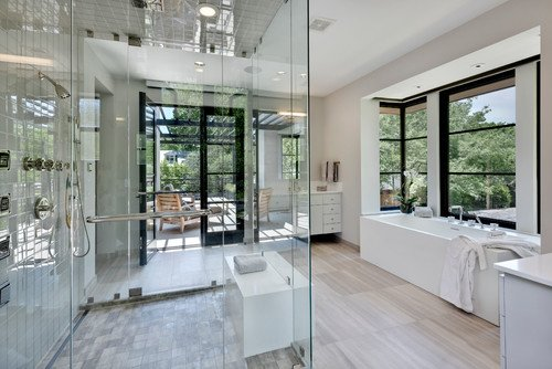 A contemporary design bathroom with white tub, enclosed shower room, wooden flooring and flat panel cabinets for essentials. / Photo by Stocker Hoesterey Montenegro