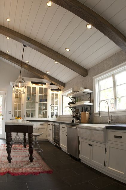 This L- shaped kitchen has its beams as the focal point as the contrast of wooden ceiling and its beams have contrasting colors.