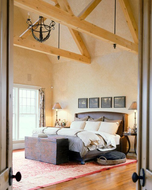 A wrought iron chandelier and light-toned wooden rafter accentuate this master bedroom's vaulted high ceiling. Photo by Witt Construction