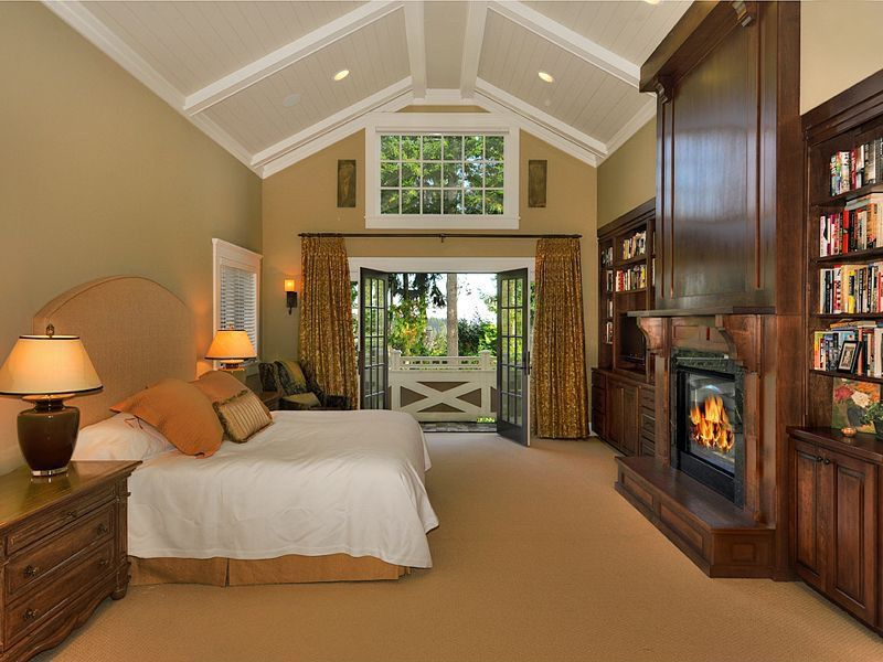 This primary bedroom offers a large bed and fireplace, along with brown carpet floors and walls with a high ceiling.