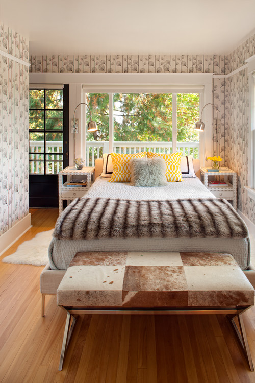 A set of French door and windows frame the natural outdoors as scenic interest for this master bedroom.Photo by Vanillawood