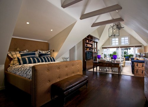 A whitewashed vaulted ceiling with gray-painted beams and fancy chandelier creates a dramatic setting for this open concept master bedroom.Photo by DD Ford Construction