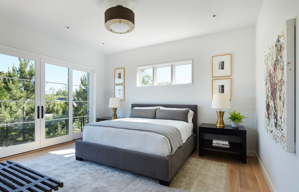 Whitewashed walls and glass doors fill up this master bedroom in light and airy atmosphere.