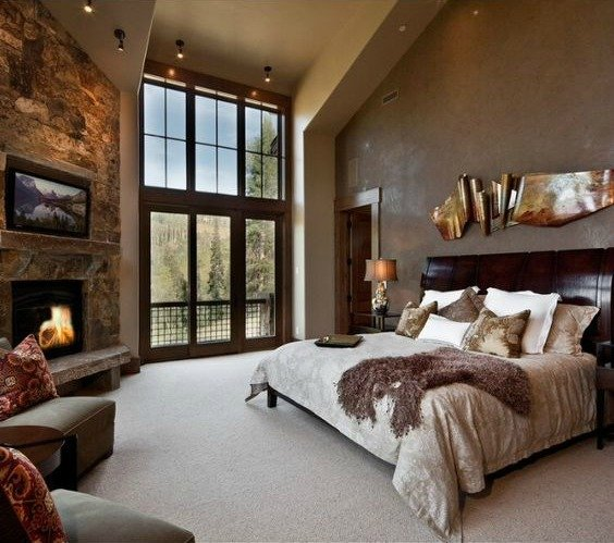 Medium-sized primary bedroom with a stylish fireplace and a large bed set on the room's carpet flooring.