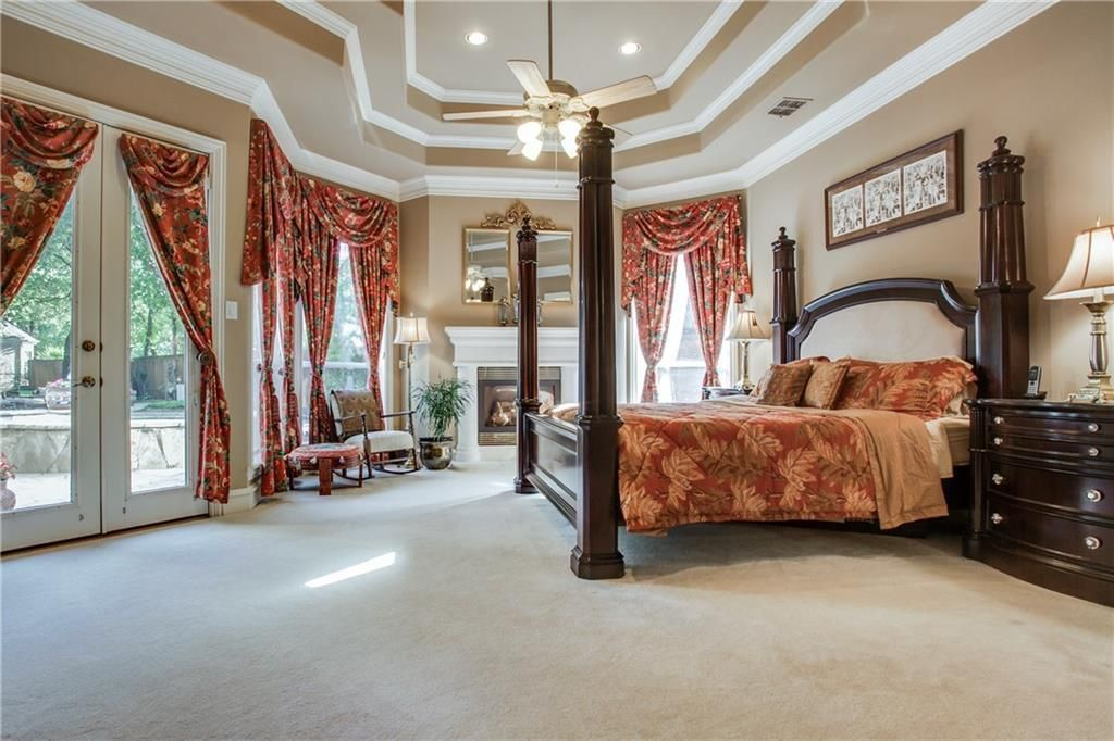 This bedroom features a luxurious bed and a fireplace, along with carpet floors and a stunning ceiling.