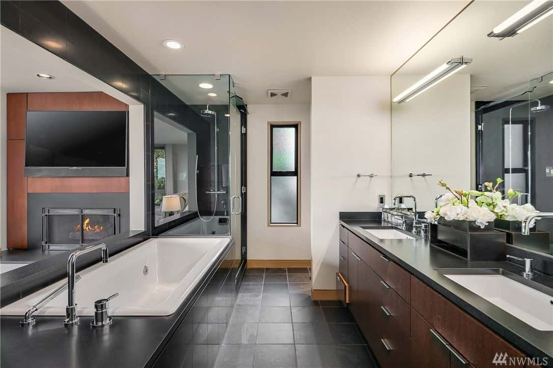 A simplistic design, this gorgeous bathroom uses cool cream, white, and light gray in combination with dark colored hardwood floors for an amazing simple but chic finish.