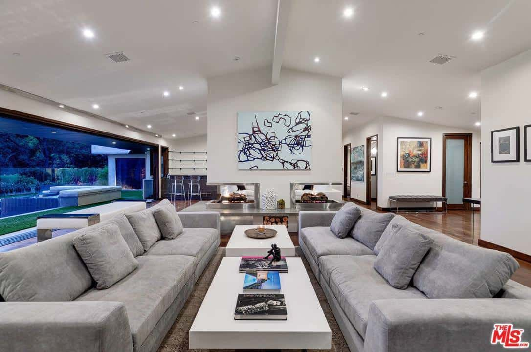 This modern living room looks larger than it actually is because of the large wide wall to wall windows and a light color scheme décor. The choice of art, clean lines of the ceiling and couches are all modern elements of design.