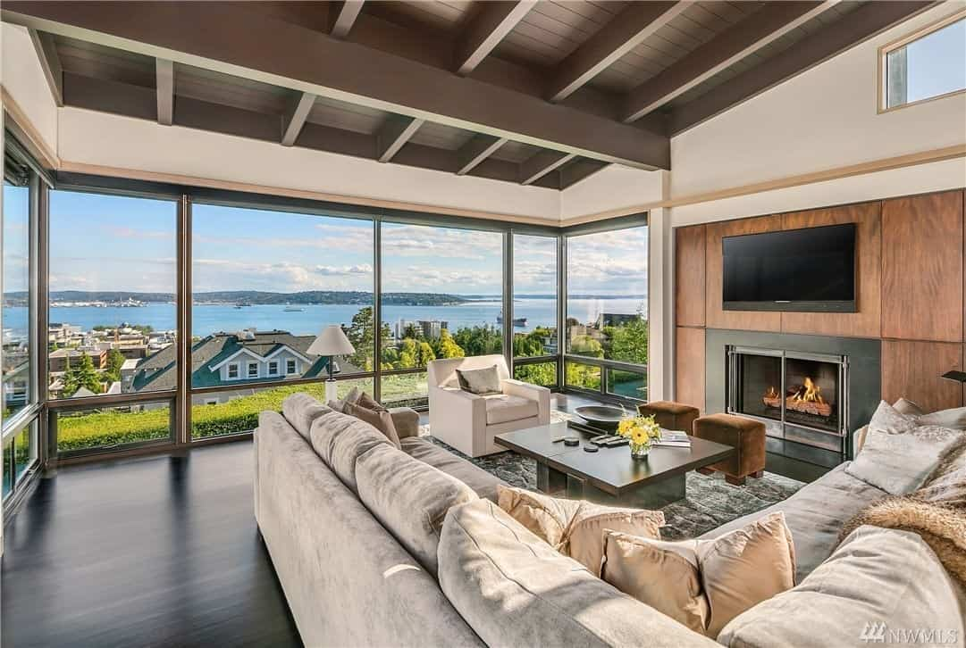 This living room comes off as a cozy family room with the large L shaped couch. True to modern design, it has minimal décor and plenty of natural light from floor to ceiling windows and skylights.