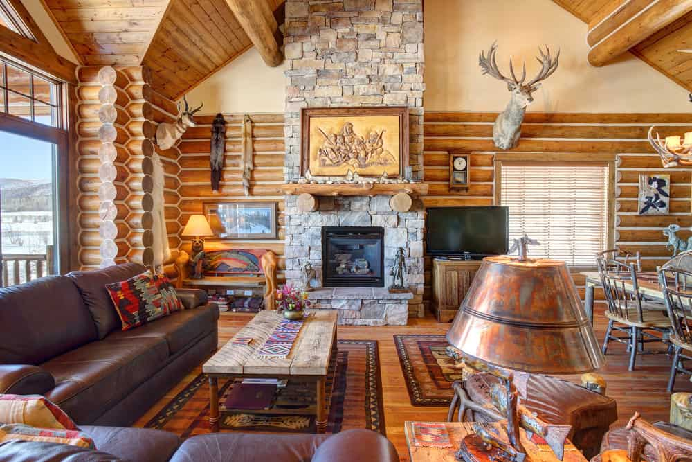 Rustic Family Room With Stone Fireplace Inside Large Log Home.