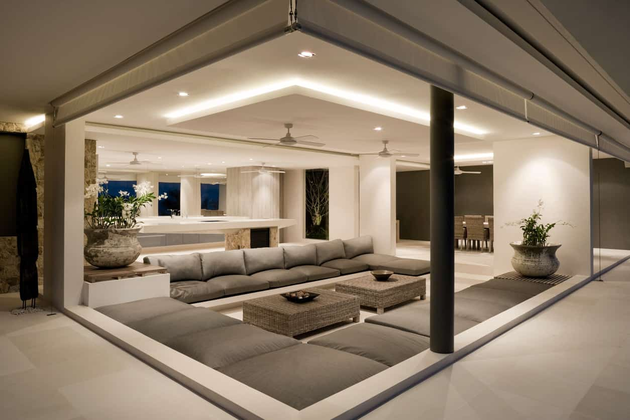 Super cool modern living room in villa with floor-to-ceiling windows and built-in sectional sofas all in brown and beige.