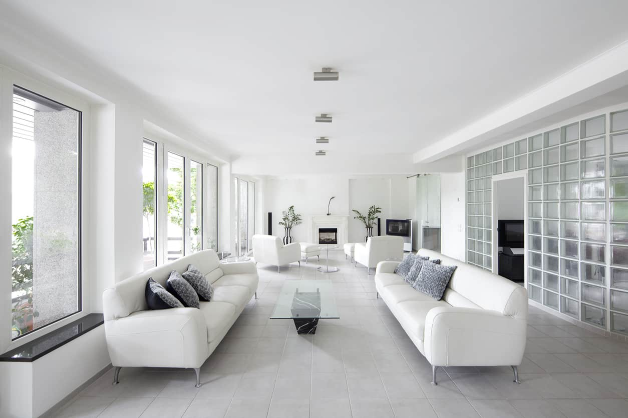 This large living room has been divided into two 'lounges' so to speak with symmetrical placements of furniture and cushion. The effect is very chic!
