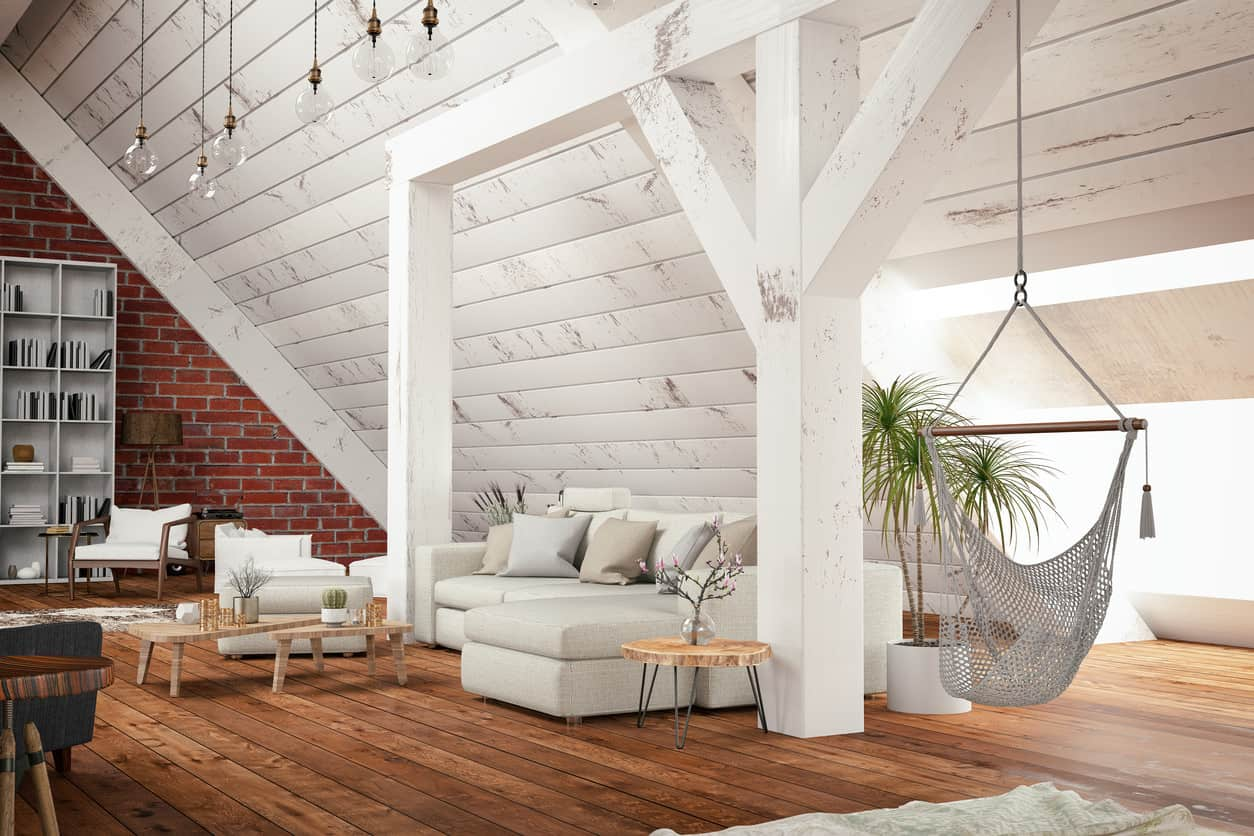 This gorgeous living room is contemporary but uses some classic farmhouse like elements a hammock and white wooden ceilings for a loft style look that is cozy and unbothered.