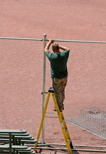 Man constructing a chain link fence