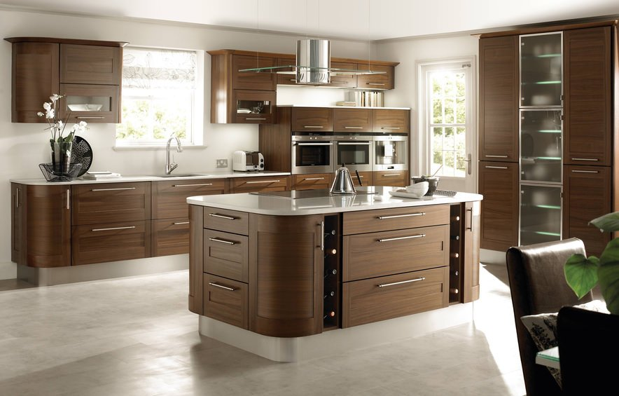 Large Mediterranean kitchen with white walls and floors. It also features brown cabinetry. The center island looks great and perfectly placed.