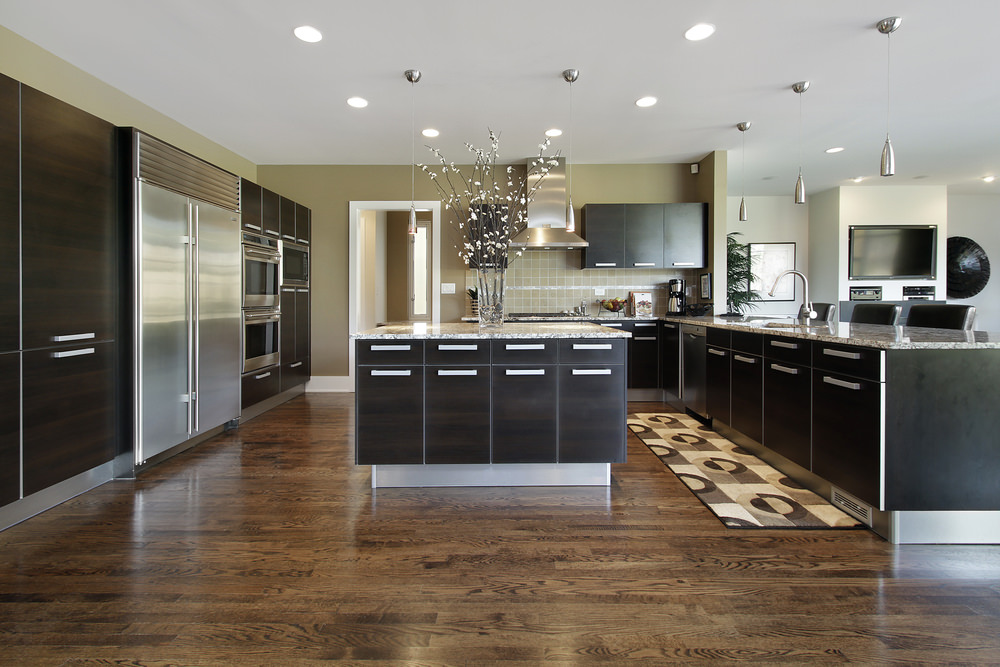 Spacious kitchen features dark wood cabinetry and breakfast island with marble countertops. It has hardwood flooring topped with brown patterned kitchen runner.