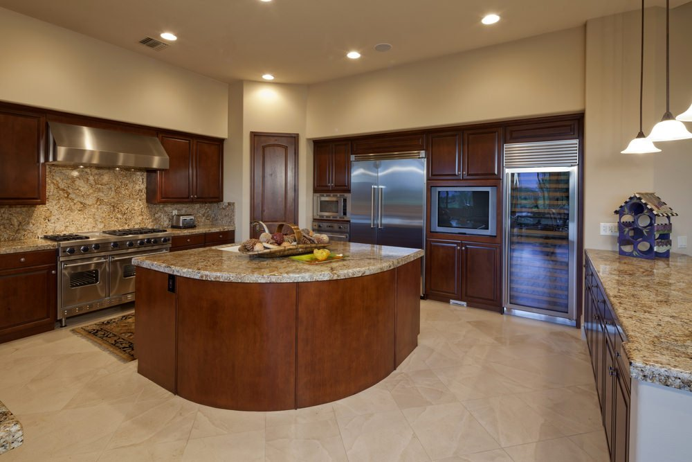 This kitchen features tiles flooring and a regular ceiling, along with a stylish center island and kitchen counters with granite countertops.
