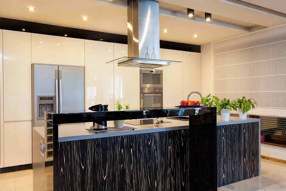 The sleek kitchen offers a stainless steel vent hood suspended over a stylish kitchen island framed with raised high gloss black counter.