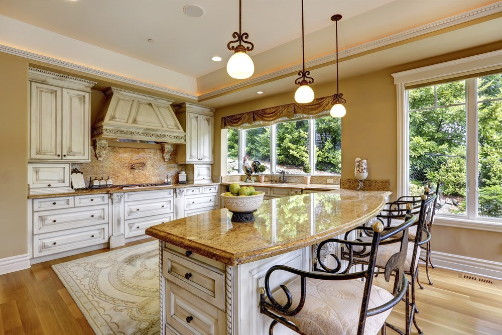 Classy kitchen with hardwood flooring topped by a white rug and glass paneled windows dressed in gold valence. It has a curved peninsula aligned with ornate metal chairs that are fitted with cream foliage cushions.