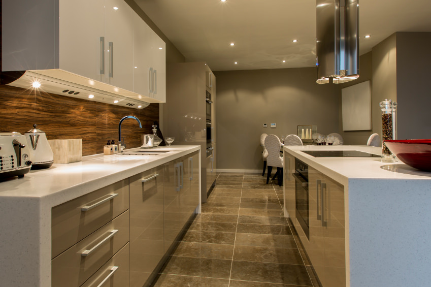 Modern kitchen setup featuring smooth white countertops on kitchen counters and center island. The tiles floors look glamorous. The recessed lights look perfect as the room's lighting.
