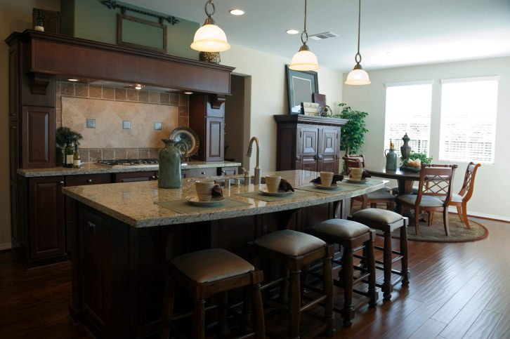 A classy single wall kitchen boasting a large center island providing space for a breakfast bar lighted by pendant lights.