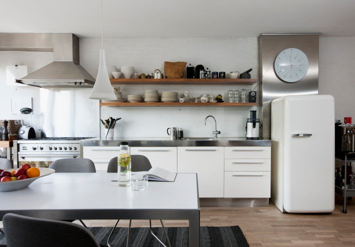 This Scandinavian-Style kitchen features a hardwood flooring topped by a stylish rug. There's a dining table set on the middle. The white fridge matches well with the white counters.