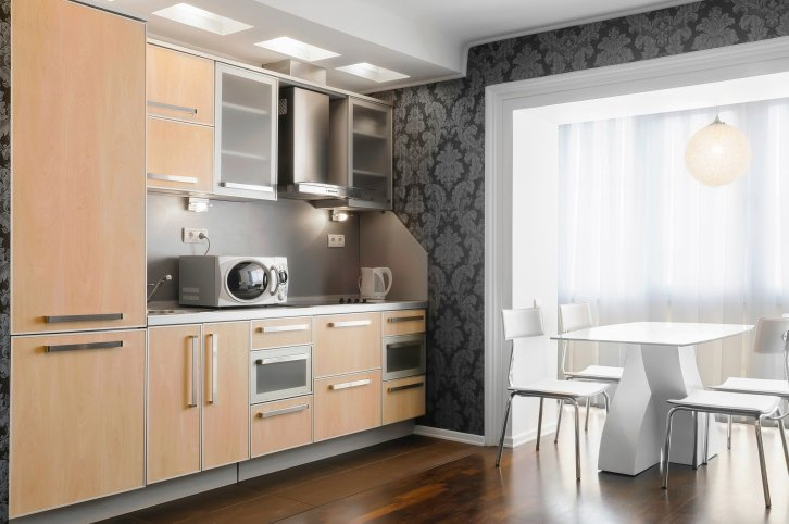 This single wall kitchen boasts elegant walls and classy hardwood flooring. There's a small dining nook as well, featuring stylish table and seats.