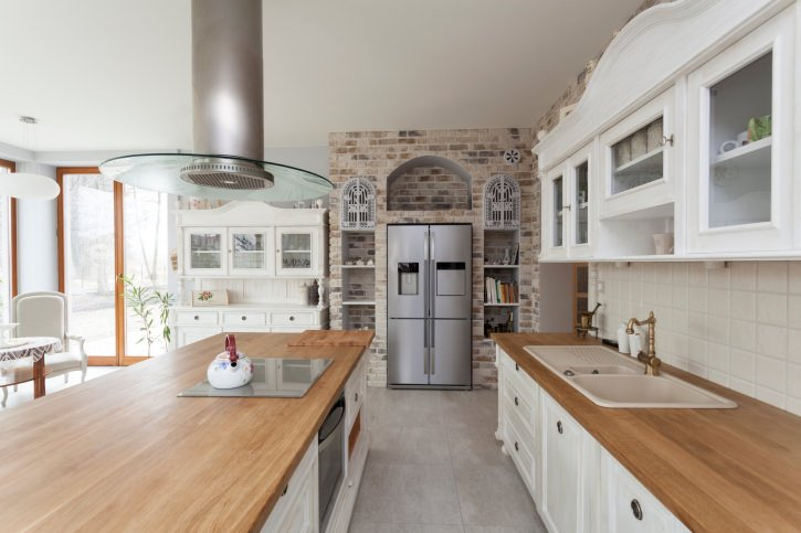 Light and airy kitchen with white cabinetry, white tile backsplash, wood countertops, an accent brick wall with open shelving, and a surrounding wood-framed glass doors.