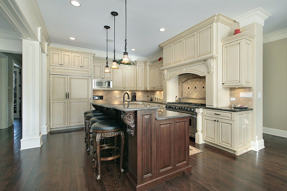 An L-shaped kitchen featuring a breakfast bar with classy bar stools and is lighted by pendant lights.
