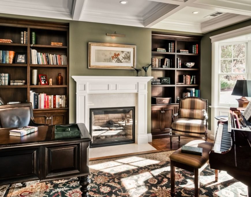 This gorgeous office is an example of a home office I would love to have with the hardwood floor, area rug, fireplace, floor-to-ceiling shelves and a piano to boot.