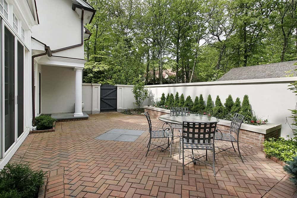 Brick patio with herringbone pattern. There's a small dining area on the side.