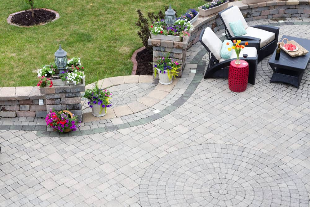 Brick patio pattern combo whorled and pinwheel floors. There's a pathway leading to the lawn area along with lounging space on the side.