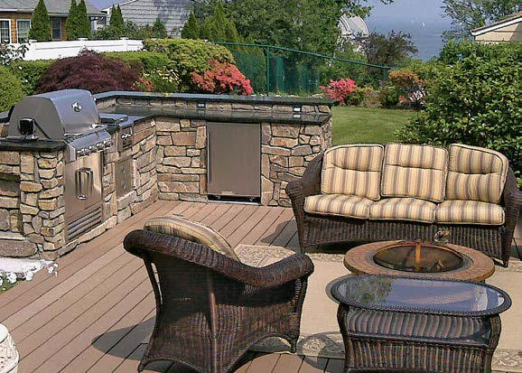 This outdoor kitchen provides a lounging space with a fire pit, along with a bricks-made bar with granite countertops.