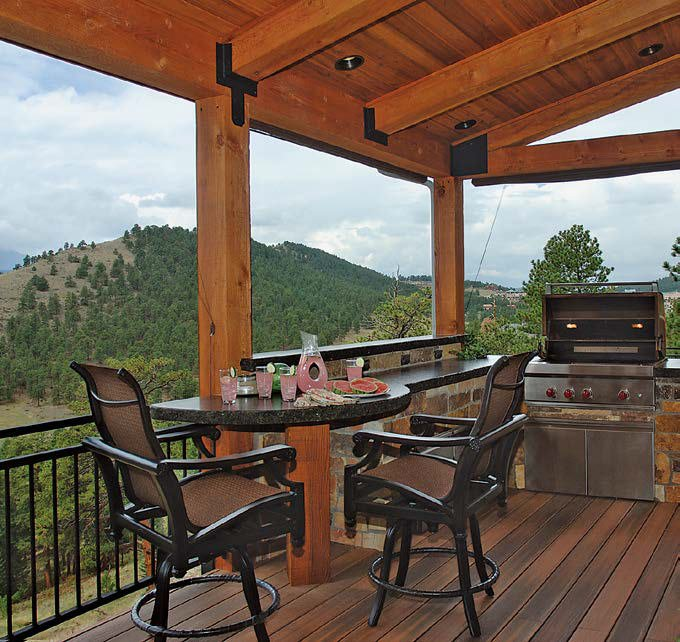 This glamorous outdoor kitchen set on the home's elevated deck features a stylish bar with granite countertops.