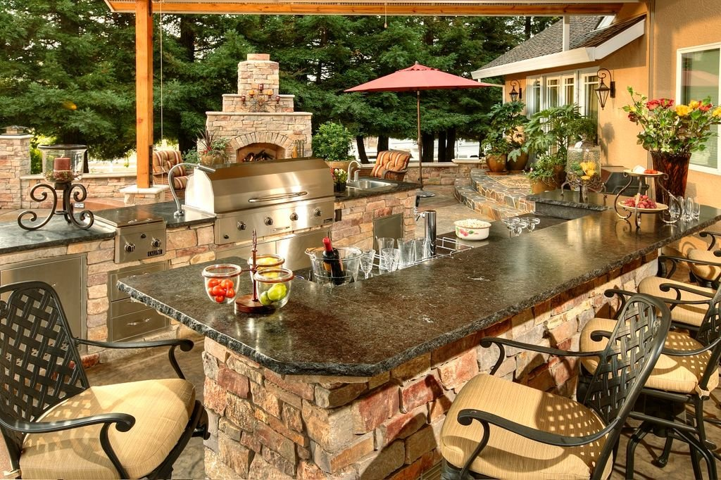 This outdoor kitchen offers a classy bar counter with a granite countertop, perfect for drinking with family and friends.