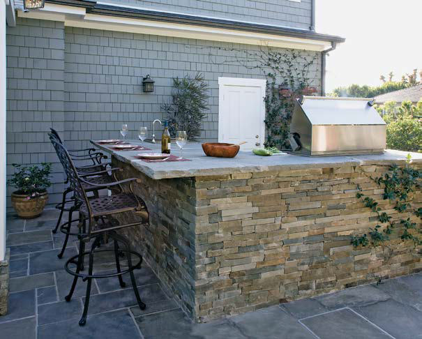 This outdoor kitchen features a large bar made of bricks topped by smooth countertop providing space for a drinking bar.