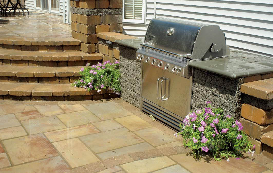 Beautifully structured outdoor kitchen with a bar made of bricks and topped by smooth counter.