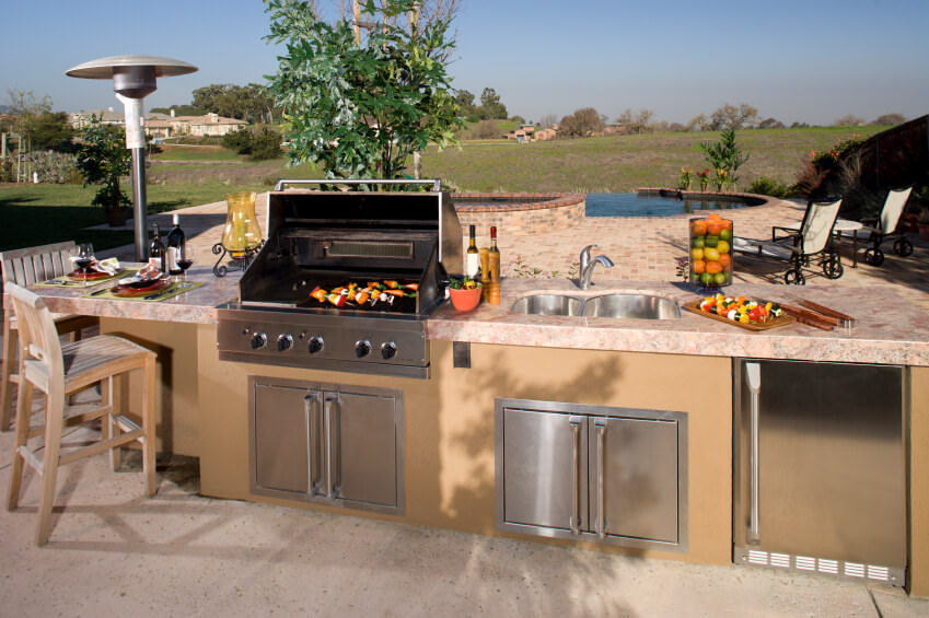 This outdoor kitchen boasts a large bar and counter with top-of-the-line appliances.