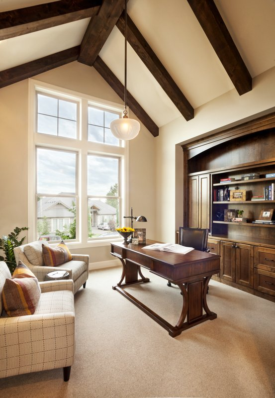 A classy home office with elegant chairs and a luxurious desk set on the carpet flooring. The room features a vaulted ceiling with exposed beams lighted by a pendant lighting.
