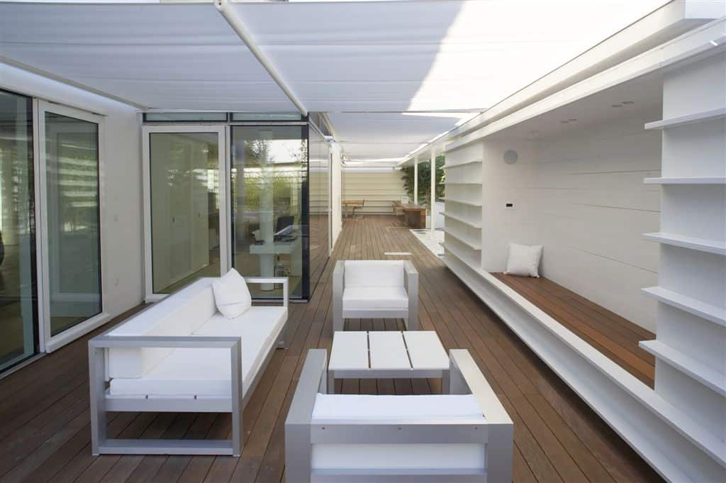 Covered deck featuring white seats and a bench seating.