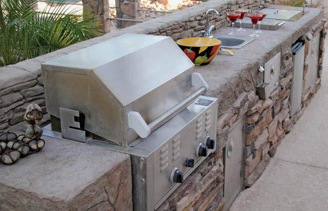 This outdoor kitchen features a long bar setup equipped with stainless steel appliances.