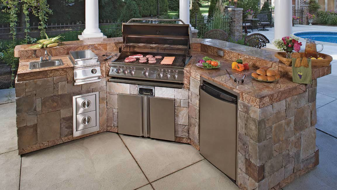 This outdoor kitchen features a stylish stone brick bar with an elegant-looking countertop.