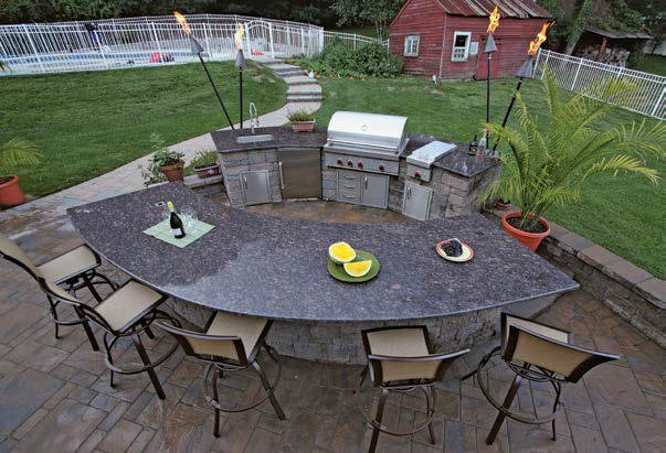 This outdoor kitchen features a small bar and a large counter providing space for a breakfast bar. The countertops look glamorous.