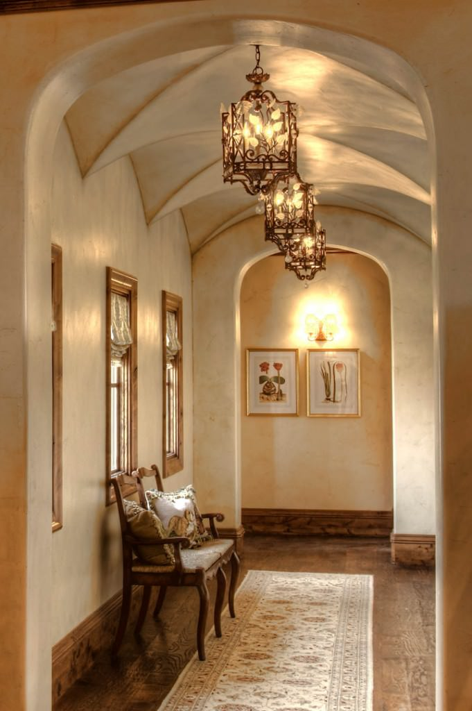 This foyer features a groin-vault ceiling lighted by elegant ceiling lights. The chairs on the side looks classy.