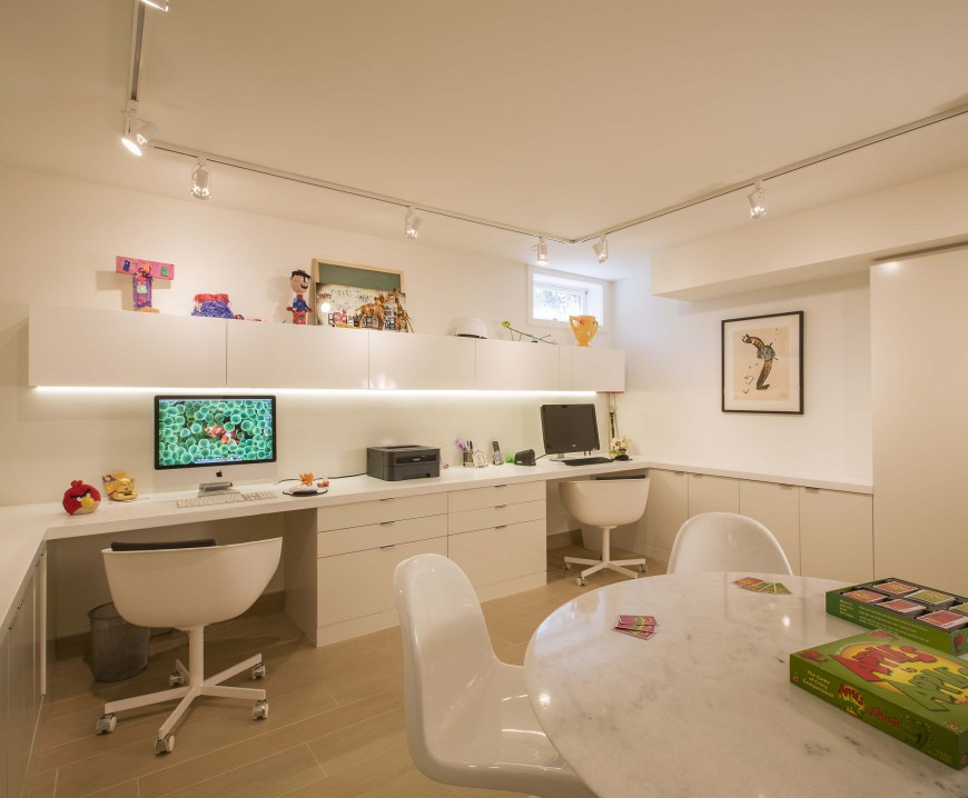White home office boasts a sleek floating shelf mounted above the built-in desk that's fitted with drawers and chairs. It also has a seating area with a marble table and glossy white chairs.