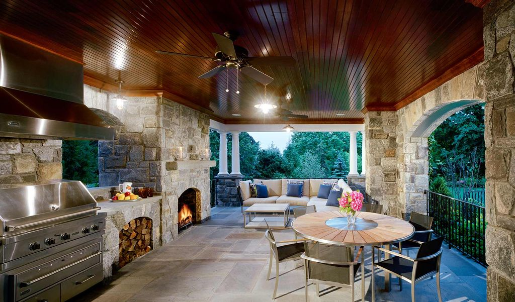 Large outdoor kitchen area featuring a dining table set and a living set near the fireplace.