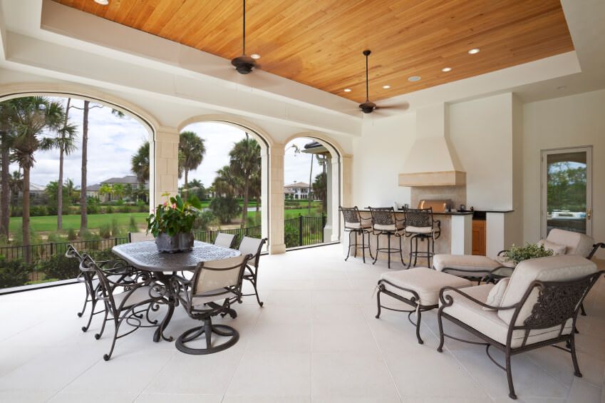 Large outdoor kitchen featuring a bar and counter along with a dining table set and lounger seats.