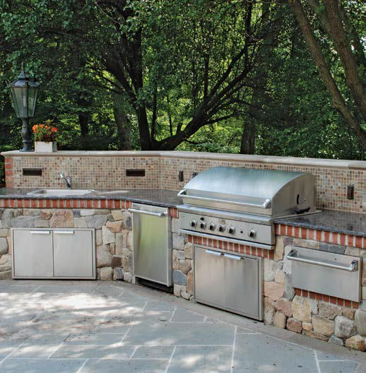This outdoor kitchen boasts a long bar setup made of large stones and granite countertop.