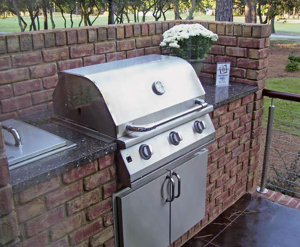 A close up look at the outdoor kitchen's stone brick bar with a granite countertop along with a grill stove.
