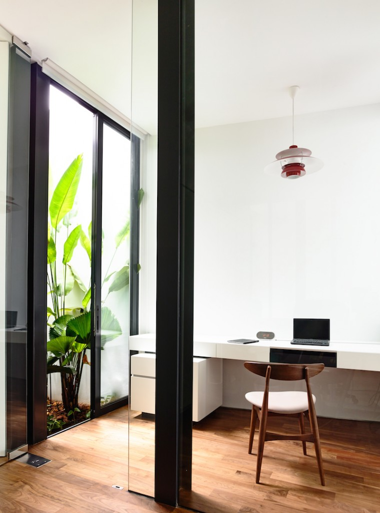 This home office showcases a white desk and wooden chair along with wood plank flooring and glass door that opens to a green yard.