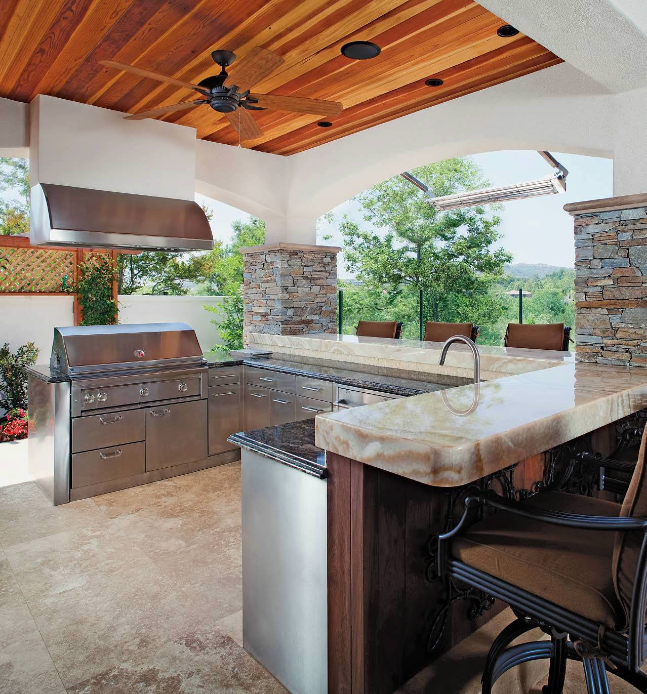 Outdoor kitchen with a large bar area featuring a combination of granite and marble countertops.